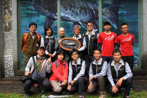 雪霸國家公園理處長鍾銘山(左四)贈送櫻花鉤吻鮭紀念品給國際保育大使珍古德博士(左三)。(雪霸國家公園管理處提供)
