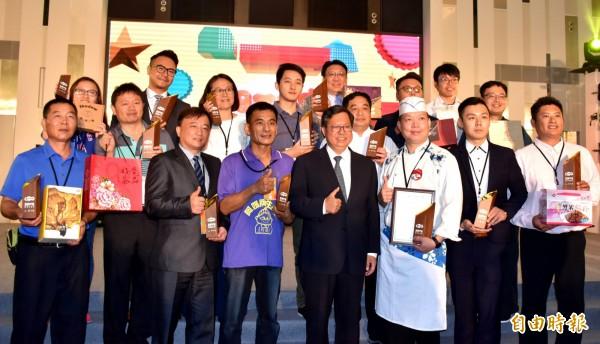 鄭文燦(前右4)與獲獎「金牌好禮」的店家合影,圖前右3為五連霸的「新百王餐廳」主廚簡境宏。(記者李容萍攝)