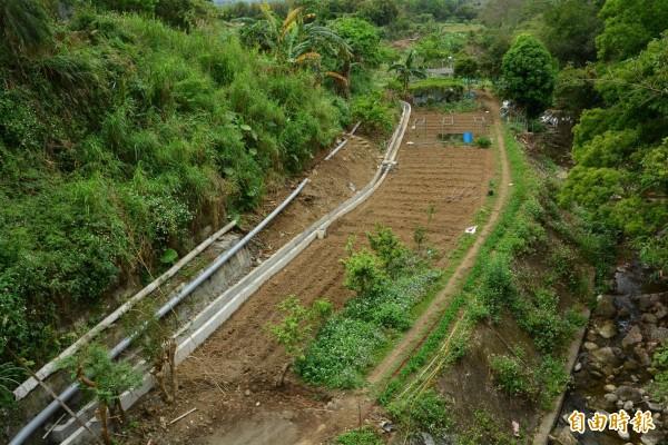 從四寮溪(右)崇德橋向下游看,圖左下農民抽水灌溉的管線,跟新竹農田水利會新做好的灰白水泥圳路並行,質疑者質疑圳路工程的必要性,水利會強調這是當地納入灌區的前置準備。(記者黃美珠攝)