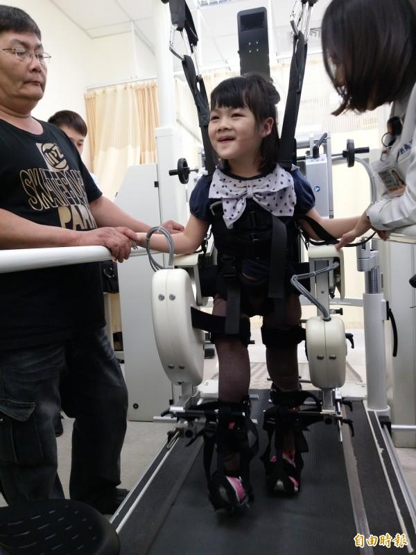 藉由機器人步行訓練,小欣(中)已能自行站立。(記者吳亮儀攝)
