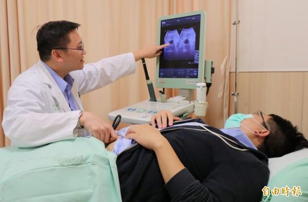 亞大醫院震波碎石室主任石欣衛(左)替患者掃膀胱超音波,提醒多喝水、多吃蔬果、少憋尿,可預防膀胱癌上身。圖為情境照,圖中人物與本文無關。(記者陳建志攝)