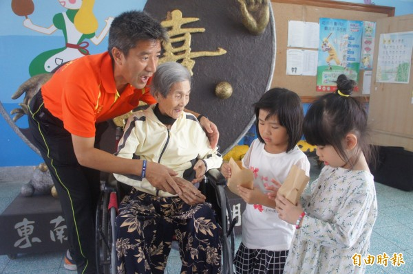 湖西鄉長吳政杰陪同為夫尋根圓夢的老婦,一同發放免費雞蛋糕。(記者劉禹慶攝)