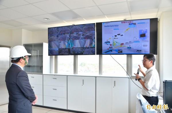 代理市長李孟諺(左)從監控螢幕中,瞭解自駕車測試情況。(記者吳俊鋒攝)
