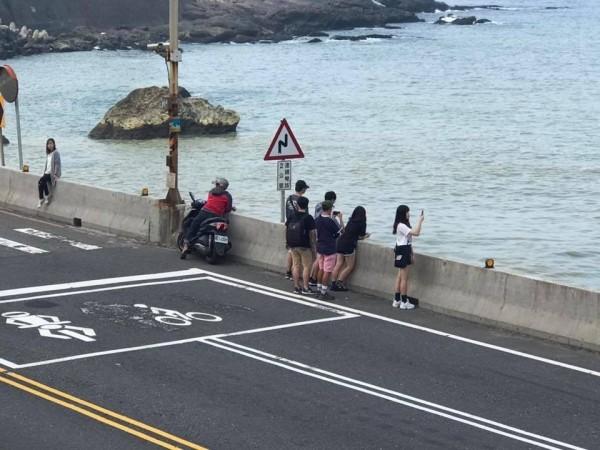 遊客在馬路邊拍攝陰陽海美景,險象環生。(記者林欣漢翻攝)