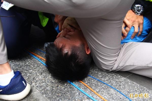 該名抗議男子被警方壓制在地。(記者邱書昱攝)