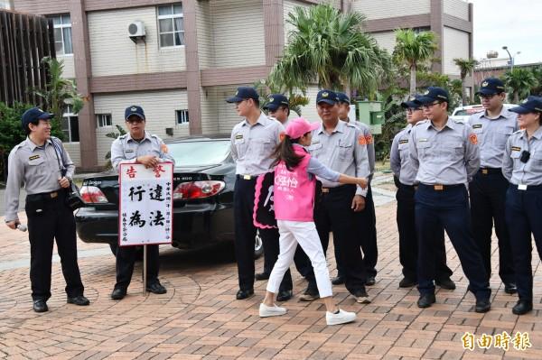 張怡到恆春鎮公所前宣示反黑,險遭警方舉牌警告。(記者蔡宗憲攝)