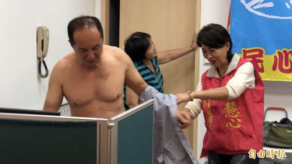 台南市長候選人林義豐今天到桃園為市議員候選人袁慧心打氣,現場脫衣換裝。(記者陳昀攝)