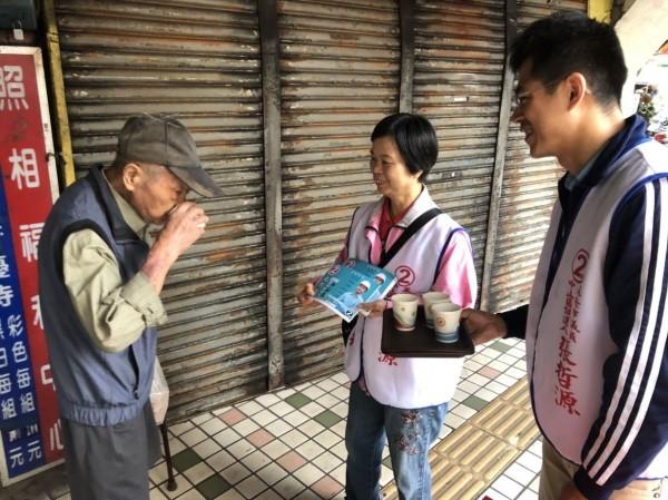 基隆市中山區無黨籍議員候選人張哲源(右)與選民分享「沖沖沖」的咖啡,走過的路人喝著咖啡分享美好。(記者俞肇福翻攝)