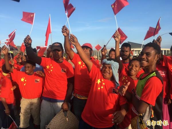中國捐贈巴紐的「獨立大道」揭幕,中方贈送五星旗、及印有五星旗及「歡迎習近平主席」的T恤給民眾。(記者黃佩君攝)