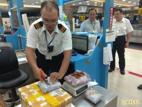 林聰賢(後排左)視察過程,防疫人員查獲越南新住民攜帶肉製品(前)入境,當場沒收、開罰。(記者洪定宏攝)