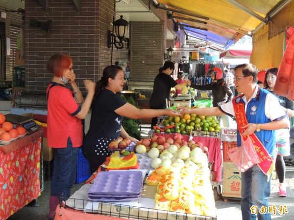 國民黨南投縣長候選人林明溱(右)到菜市場掃街,向民眾問候博感情。(記者劉濱銓攝)