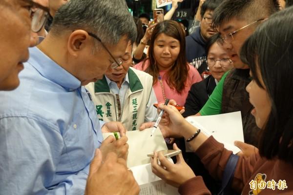 台北市長柯文哲晚間到延三夜是掃街,有支持者直接拿手機當簽名版用。(記者沈佩瑤攝)