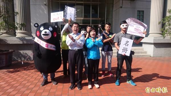 民進黨台南市長候選人黃偉哲(前左)和第一選區市議員候選人賴惠員(前右),在台南市警察局門口表達反賄選訴求。(記者楊金城攝)