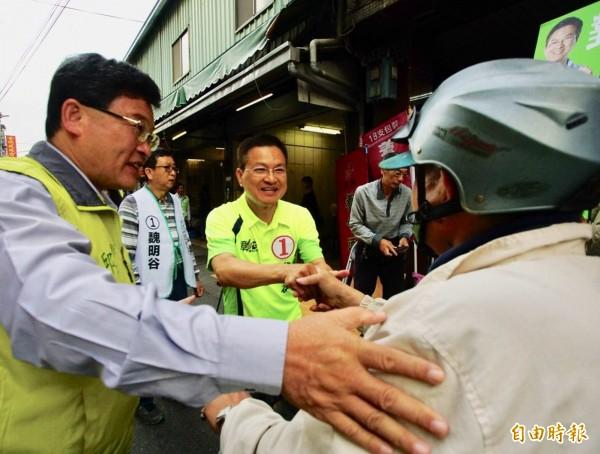 民進黨彰化縣長候選人魏明谷(中)在彰化市傳統市場向菜販與菜籃族緊握雙手拜票懇託。(記者湯世名攝)