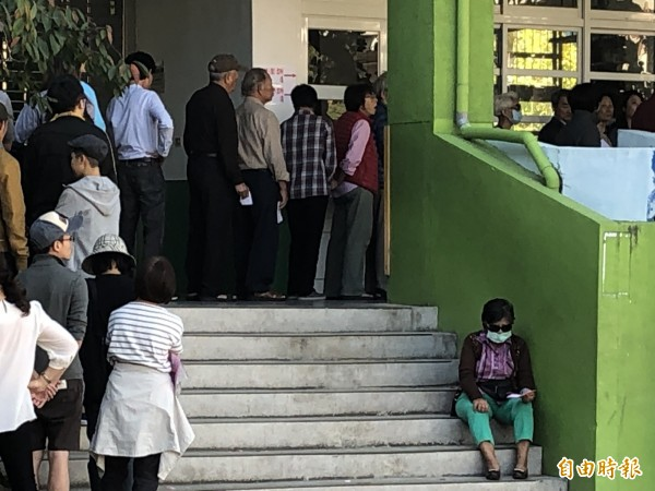 在北屯區松竹國小投開票所,因等候投票的人大排長龍,有長輩腿力不支,乾脆先坐在樓梯上等。(記者歐素美攝)
