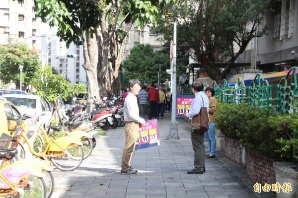 許多投開票所外面都出現愛家團體在外面舉看板宣傳愛家公投。(記者鍾泓良攝)