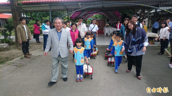 南市副市長張紹源(前左一)、社會局長劉淑惠(前右一)牽著小朋友的手,一起拖著裝有尿布、奶瓶、嬰兒鞋等物品的小推車,進入麻豆大山公共托育家園內,象徵幸福送入家園。(記者楊金城攝)