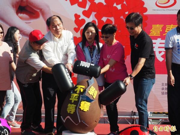 台東縣身心障礙者公益園遊會上,身心障礙者福利團體代表手持槌子,象徵合力破除「剝奪不平等」的不利環境。(記者王秀亭攝)