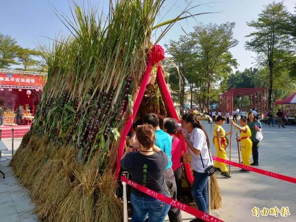 新港文教基金會義工用白蘿蔔、甘蔗、玉米、花生、稻穗、鳳梨等搭建「雙合寮仔」,讓參與民眾過平安隧道。(記者曾迺強攝)