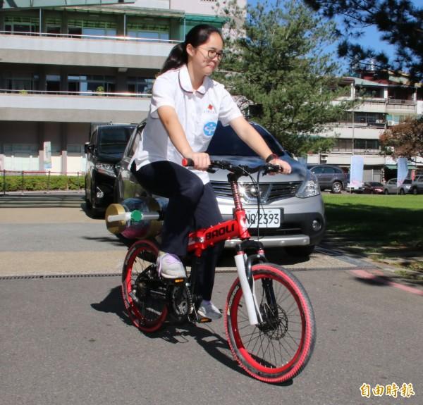 國立暨大附中女學生簡詩婷發明自行車環保洗衣裝置,示範邊輕鬆騎單車邊洗衣服。(記者張協昇攝)