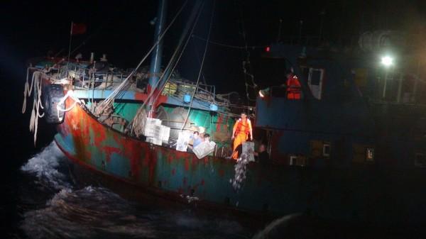 中國漁船越界捕撈,海巡署人員登船檢查,並將船上漁獲倒入海中。(記者歐素美翻攝)