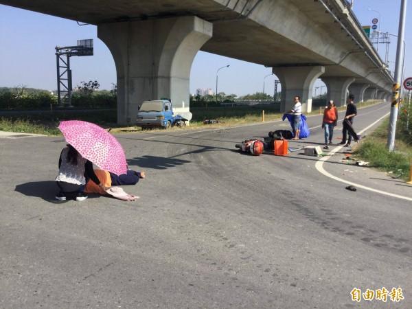 熱心路人拿傘幫躺在馬路上的。(記者林宜樟翻攝自臉書社團朴子民意觀察站)