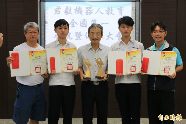 君毅中學學生彭文哲(左二)參加機器人世界賽奪銀牌、彭郁齊(右二)則在全國賽奪金,校長林慶旺(中)特頒發獎金鼓勵。(記者鄭名翔攝)