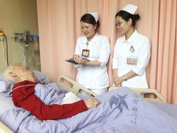 衛福部台北醫院推動「照服員共聘制」,以一對多的模式,輪三班提供廿四小時照護,家屬負擔費用減半。(衛福部台北醫院提供)