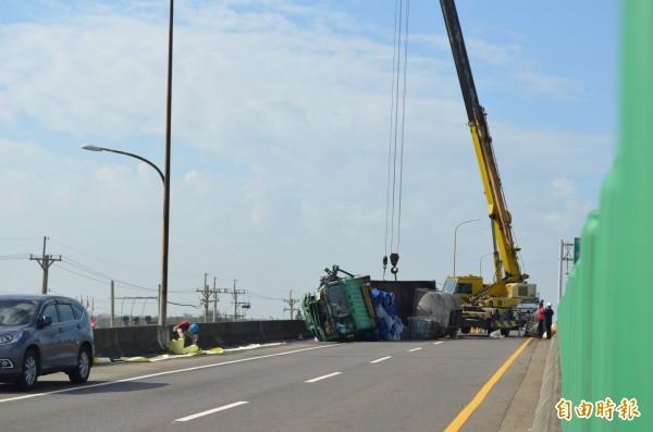 台61線台西段發生載運油桶貨車翻覆,出動吊車處理。(記者林國賢攝)