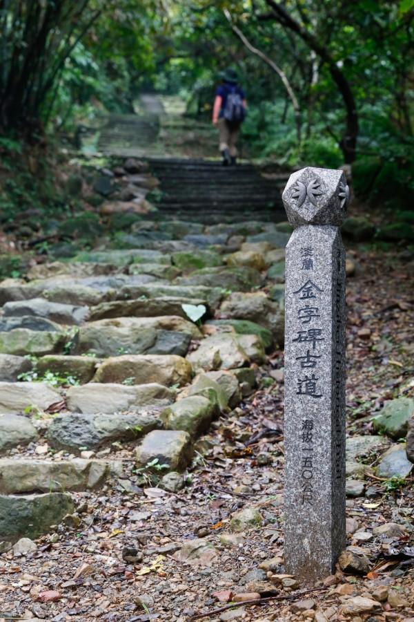 設計師蕭青陽以「淡蘭古道」少有的「雙扇蕨」設計標誌,而石柱則是邀請國寶級書法家周良敦揮毫撰寫。(新北市觀光旅遊局提供)