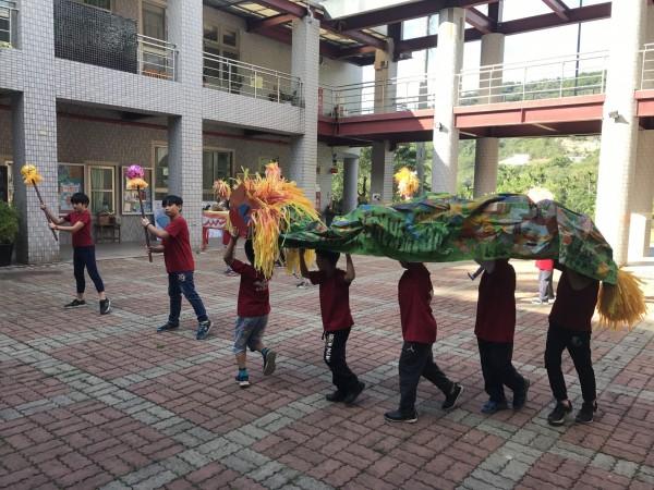 長福國小學童表演客家元宵傳統節慶(火旁)龍,請翁蔡文姊姊欣賞。(長福國小提供)