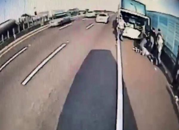 出殯車隊上國道,王姓遊覽車司機突昏迷撞護欄,救護人員路肩全力搶救。(記者湯世名翻攝)