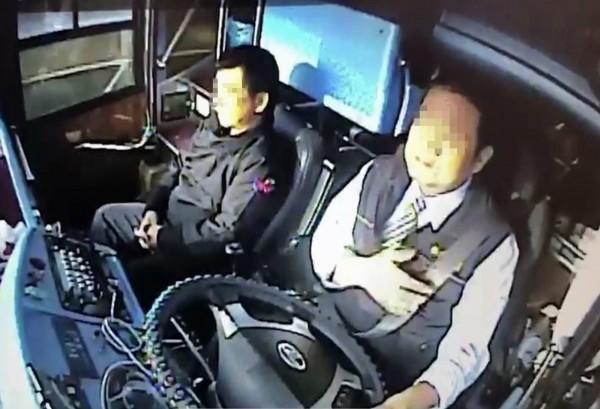 王姓司機駕駛遊覽車載運40名出殯隊伍家屬,一度用左手摀著胸口,疑似身體出現不適。(記者湯世名翻攝)