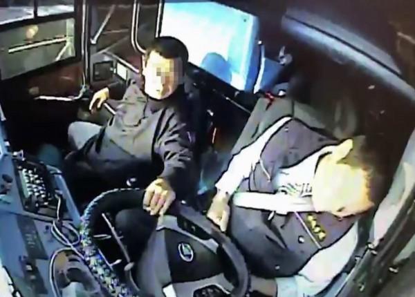 王姓司機陷入昏迷,遊覽車失控擦撞內側護欄,一旁的喪家家屬嚇得趕緊抓住方向盤。(記者湯世名翻攝)