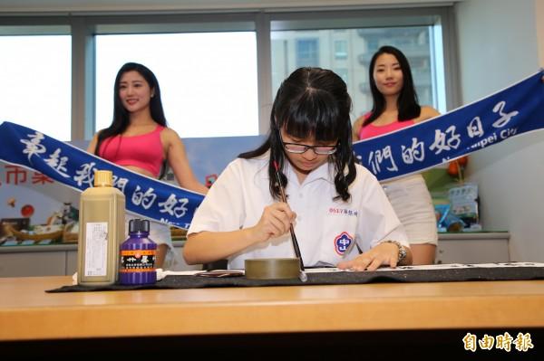元旦毛巾上印的「牽起我們的好日子」,是中山國中9年級學生林佳圻(中,寫毛筆字者)寫的行書字體。 (記者何玉華攝)