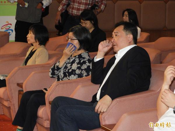 上個月辭世的高雄市前財政局長簡振澄遺孀(中),也出席記者會,掩面啜泣,高雄市代理市長許立明(右)在旁安慰。(記者葛祐豪攝)
