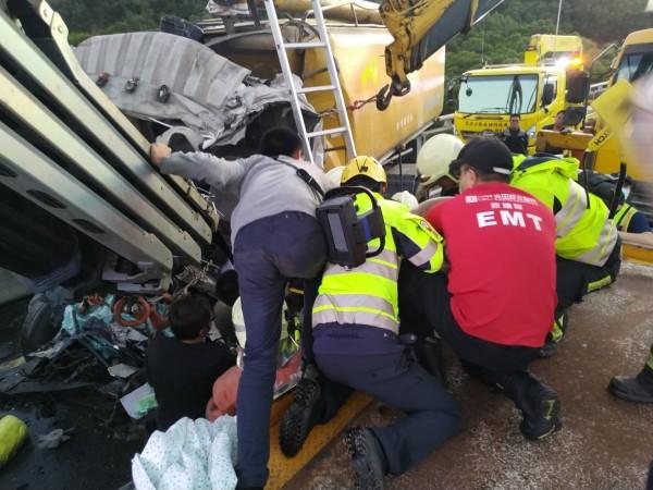 彰化消防人員經過近1個小時搶救,救出受困車內的飼料車駕駛,緊急送往醫院救治。(記者張聰秋翻攝)