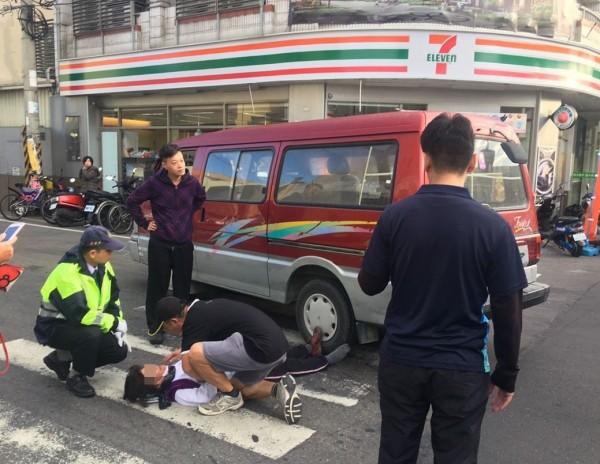 劉姓跑者不慎遭廂型車擦撞,躺在地上喊痛,一名跑者上前安撫。(記者陳冠備翻攝)