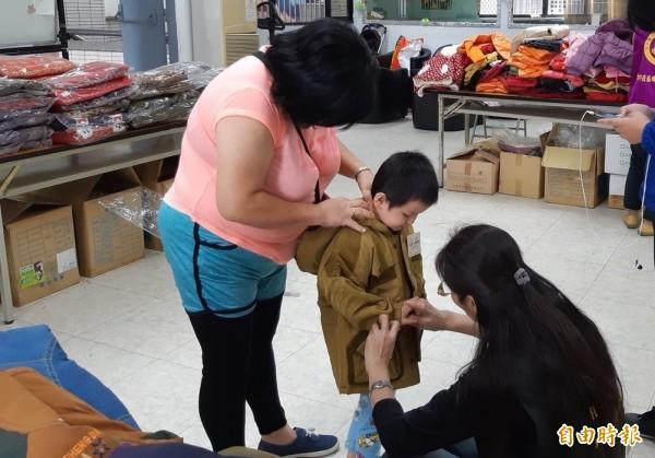家長與里長郭梅香(右)為孩童挑選外套。(記者蔡淑媛攝)