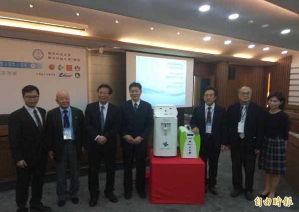 友荃公司董事長林文章(左四)贈送2台氫氧機(中)給輔英科大,由校長顧志遠(左三)代表接受。(記者洪定宏攝)