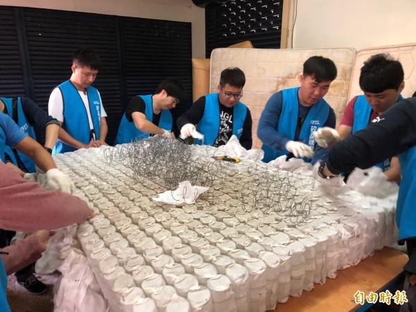 矽品志工協助幫忙拆除彈簧床。(記者張軒哲攝)
