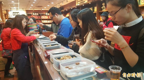 金門貢糖業者會在賣場擺上一盒盒貢糖,提供茶水給觀光客試吃。(記者吳正庭攝)