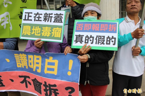 抗議團體持海報抨擊縣府有法不作為。(記者張聰秋攝)