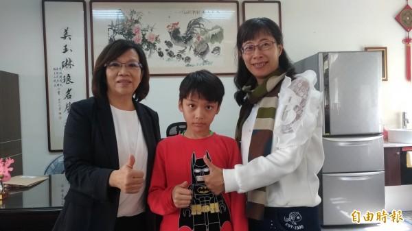 小4挑戰高年級拿下全縣桌球單打冠軍的吳京樺(中)獲虎尾國小校長張美琳(左)表揚。(記者廖淑玲攝)