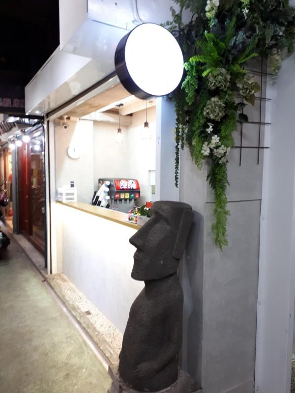 新竹市東門傳統市場內的餐飲新選擇「享噹初」,因有西式漢堡加中式麵線的雙主食,不管用餐時間或下午都有人點餐,且位在傳統市場內,西式裝潢和傳統鐵捲門的違和場景,衝擊老饕味蕾與視覺。(記者洪美秀攝)