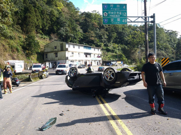 一輛保時捷雙門跑車今下午在北宜公路翻覆。(記者陳薏云翻攝)