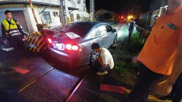 一輛汽車轉彎時受到燈光影響「轉錯彎」,在花蓮市建國路平交道鐵軌上卡住。(台鐵提供)