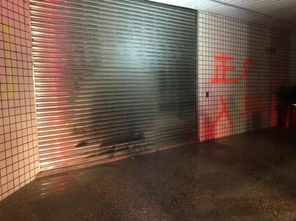 縣黨部鐵捲門和牆壁被噴上紅色字樣的油漆,鐵捲門有燒毀痕跡。(曹嘉豪提供)