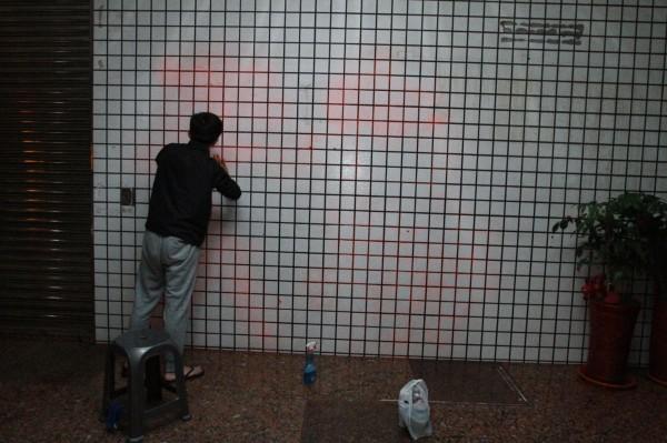 縣黨部人員清理牆壁磁磚上噴漆。(記者張聰秋翻攝)