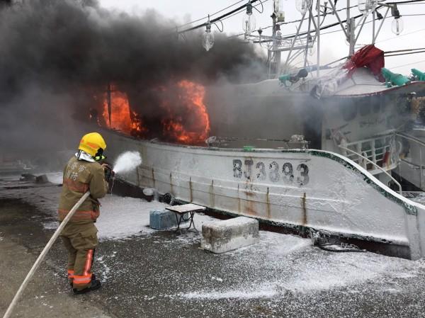 基隆市八斗子漁港內有一艘漁船下午2時30分突然起火燃燒,火勢猛烈。基隆市消防局獲報出動中正等3分隊前往搶救,消防員火速佈線控制火勢。(記者林嘉東翻攝)